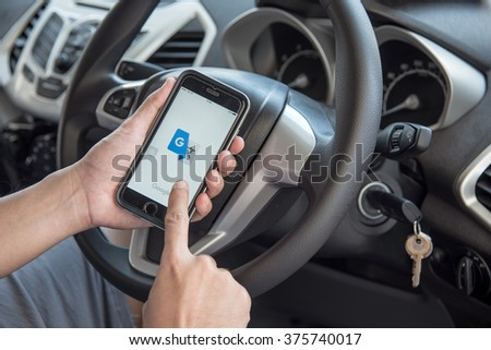 NAKORN PATHOM, THAILAND - FEB 12, 2016: A man hand holding screen shot of Google translate app showing on iPhone 6 in the car. - stock photo