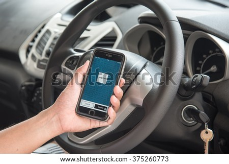 NAKORN PATHOM, THAILAND - FEB 11, 2016: A man hand holding screen shot of Uber app showing on iPhone 6 in the car. - stock photo