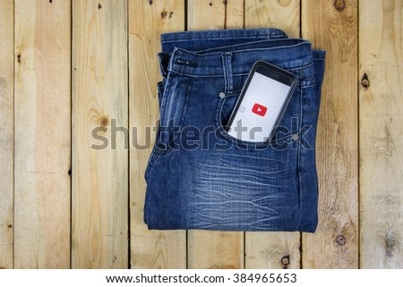 NAKORN PATHOM, THAILAND - MAR 3, 2016: Youtube app showing on iPhone 6 in pocket jean on wooden table. - stock photo