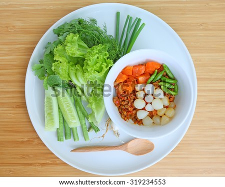 Nam prik ong and Spicy meat and vegetable on white plate against bamboo wooden board - stock photo