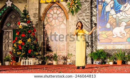 NAMDINH CITY, VIETNAM - DECEMBER 24, 2014 - An unidentified Christian singer performing a nice song on Christmas Eve in front of the Grand Cathedral. Namdinh is also famous for religious openings. - stock photo