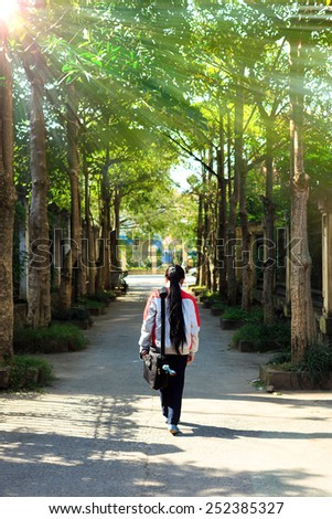 NAMDINH, VIETNAM December 18, 2014: Vietnam uniformed student go its middle two rows of beautiful trees. - stock photo