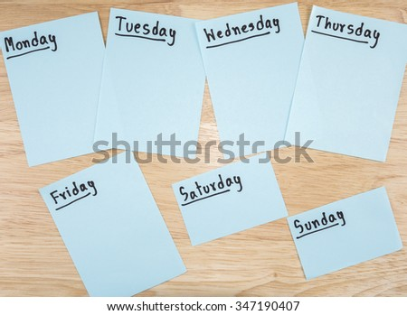 Name of 7 days in paper note on wood background - stock photo