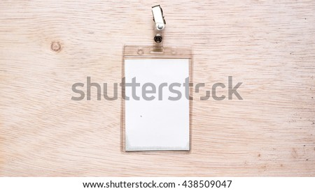 Name tag or identification holder with metal clip on wooden surface. Isolated on empty background. Slightly de-focused and close-up shot. Copy space. - stock photo