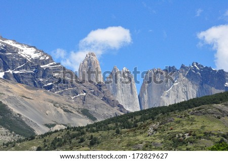 Namesake towers of Torres del Paine National Park in Chilean Patagonia peeking over surrounding mountains on a brilliant spring day - stock photo