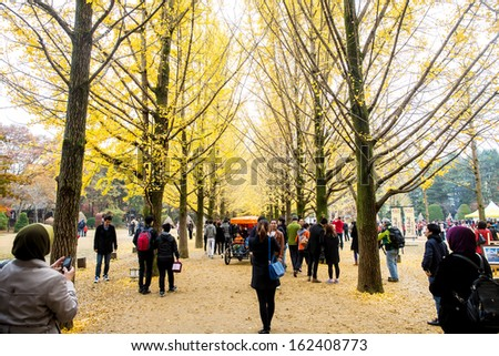 NAMISEOM - NOVEMBER 03 : Tourists visit the traditional Korean cottages on Nami Island on November 03, 2013 in Chuncheon, South Korea. - stock photo