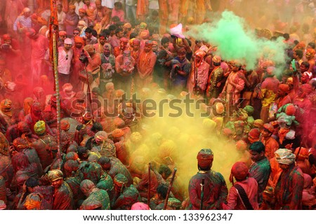 NANDGAON - MAR 22: People throw colors to each other during the Holi celebration at Krishna temple on March 22, 2013 in Nandgaon, India. Holi is the most celebrated religious festival in India. - stock photo