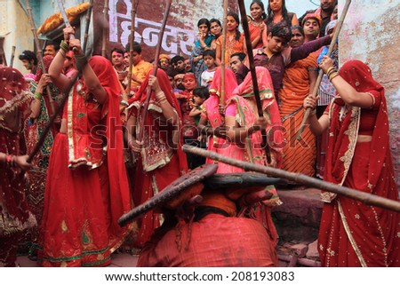 NANDGAON - MAR 22: Women beat up men with long sticks as a ritual in the Lathmar Holi celebration on March 22, 2013 in Nandgaon, India. Holi is the most celebrated religious festival in India. - stock photo