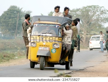 NANDIVADA,KRIHSNA DISTRICT,ANDHRA PRADESH,INDIA-DECEMBER 26:People travel in over crowded auto rickshaw  in Nandivada,krishna district,Andhra pradesh,India on December 26,2013. - stock photo