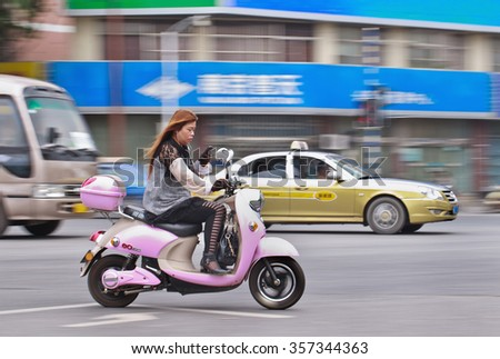 NANJING-MAY 25, 2014. Woman on e-bike busy with smart phone. China has about 500 million smart phone users and rising, using phones while driving causes an increasing number of traffic accidents. - stock photo