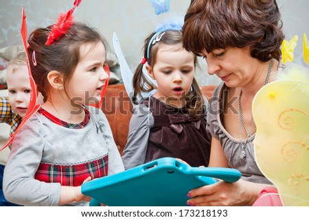 Nanny playing with children and teaching them with children`s tablet - stock photo