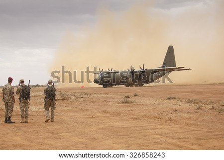 NANYUKI, KENYA - CIRCA OCTOBER 2015 - British RAF Hercules aircraft lands on field airstrip during training exercise with British Army. Government spending cuts will reduce future training like this. - stock photo