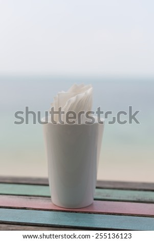 Napkins in white cup on retro wood table with blue blurred sea sky background - stock photo