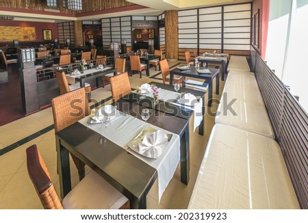 Napkins on the tables of oriental  style interior of the asian, japanese restaurant. Interior design. - stock photo