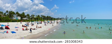 NAPLES - MAY 23: Tourists and ocals enjoy a sunny day on Naples Beach in Florida on May 23, 2015. Naples offers miles of beaches on the Gulf Coast - stock photo