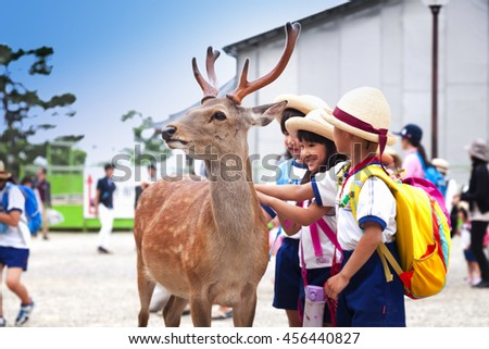 NARA,JAPAN- MAY 25, 2016:  Kids playing with wild deer in Nara on May 25, 2016. The deer in Nara have been regarded as heavenly animals, protecting the city and the country - stock photo