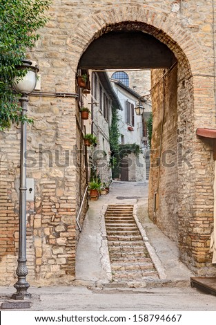 narrow alley with archway in the ancient town Bevagna, Umbria, Italy - stock photo