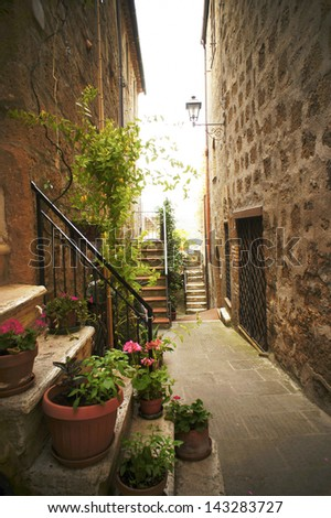 Narrow Alley With Old Buildings In Typical Italian Medieval Town - stock photo