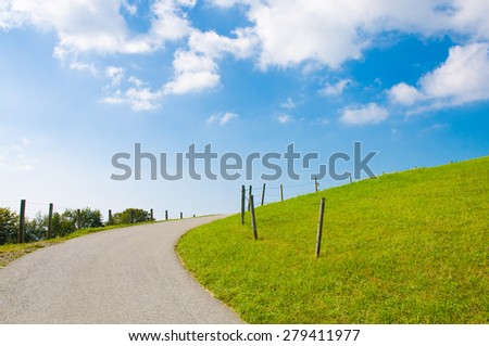 Narrow asphalt road in hilly green country under summer sky, hiking trail in alpine upland - stock photo