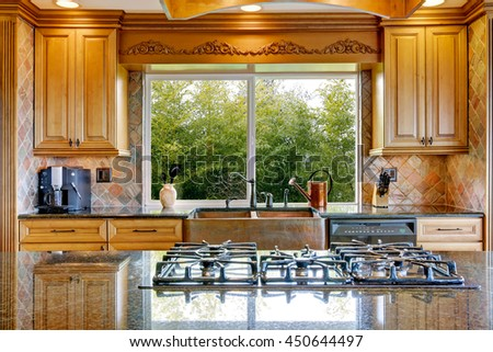 Narrow beige and yellow kitchen with cabinets and big window - stock photo