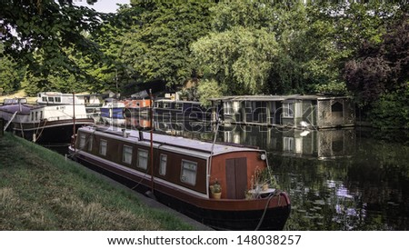 Narrow boat barge under the green trees in Cambridge, UK - stock photo