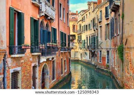 Narrow canal among old colorful brick houses in Venice, Italy. - stock photo