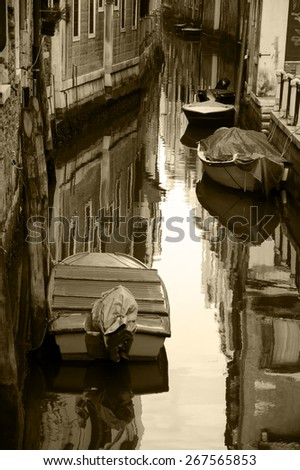Narrow canal in Venice. Boats and reflection of colorful houses in the water. Selective focus on the  reflection. Aged photo. Sepia. - stock photo