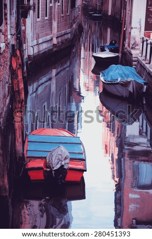 Narrow canal in Venice. Boats and reflection of colorful houses in the water. Selective focus on the  reflection. Retro aged photo. - stock photo