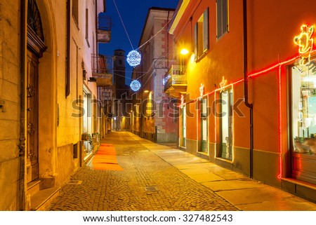 Narrow cobbled street between houses illuminated and decorated for Christmas holidays in town of Alba, Piedmont, Northern Italy. - stock photo