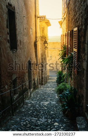 Narrow cobbled street  in the old village France. - stock photo