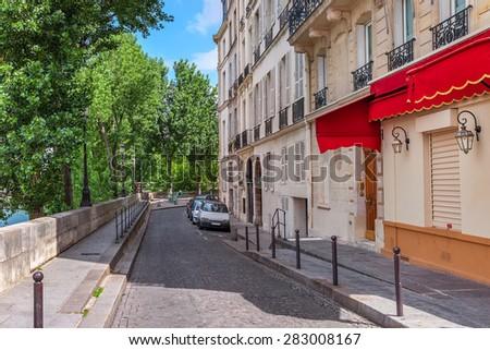 Narrow cobblestone street among green trees and parisian building in Paris, France. - stock photo