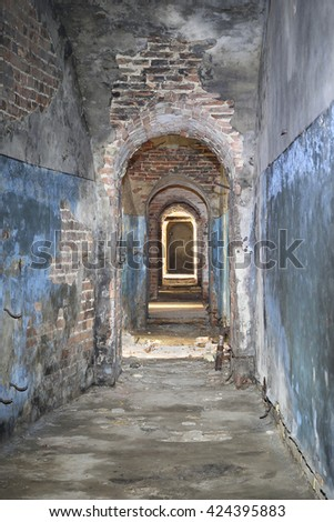Narrow corridor in old fortress basement with brick ceiling and broken stones strewn on floor - ancient dungeons - stock photo