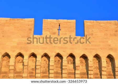 Narrow cross shaped opening in the fortified walls of the old town of Avignon, Provence, France - stock photo