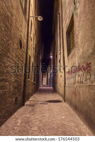 narrow dark alley in the old town - distressed alleyway in the italian city - grunge aged street at night   - stock photo
