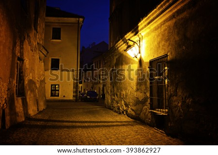 narrow dark alley in the old town - street at night in the Poland city - stock photo