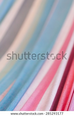 Narrow depth of field close up of striped white, purple, red, pink, and turquoise-blue fabric of hammoc.  - stock photo
