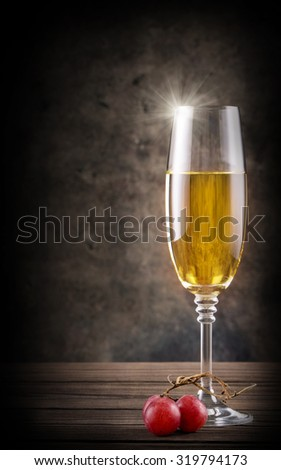 Narrow glass of a white wine on wooden table - stock photo