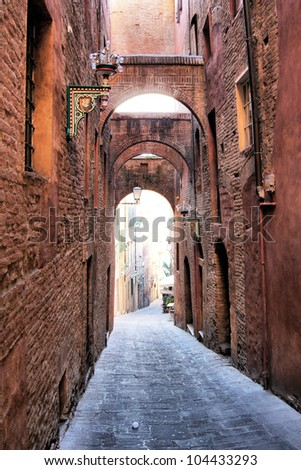 Narrow medieval arched street  - Siena, Italy - stock photo