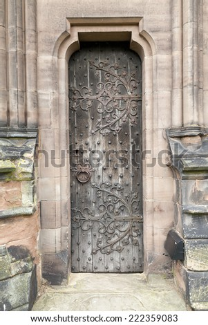 Narrow Medieval oak door with original rusting metal leaf pattern, square head nails, and door handle. - stock photo