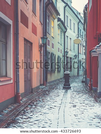 Narrow medieval street in old Riga city, Latvia. Image toned in vintage warm colors for inspiration of retro style effect - stock photo