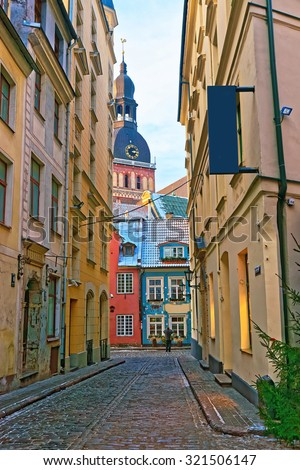 Narrow medieval street in old Riga, Latvia. Narrow streets in the capital of Latvia are often called fairylike, as they create amazing atmosphere at the Old Town. - stock photo