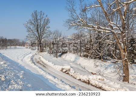 Narrow road, trees and rural field covered with snow in Piedmont, Northern Italy. - stock photo