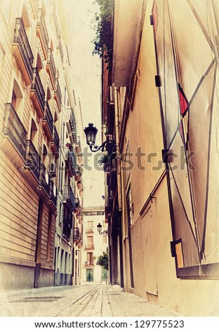 Narrow spanish street. Photo in old image style. - stock photo