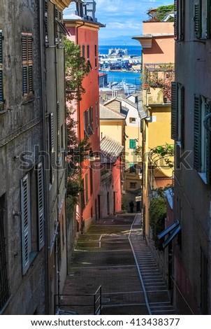 Narrow steep alley in the city center of Genoa - stock photo