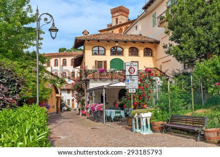 Narrow street and houses with flowers in Barolo - small town in Piedmont, Northern Italy. - stock photo