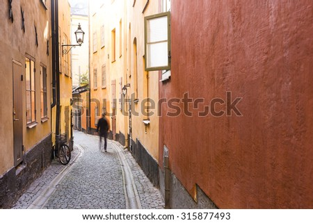 Narrow street in the Old Town of Stockholm, with open window, parked bicycle and person walking in blurred motion - stock photo