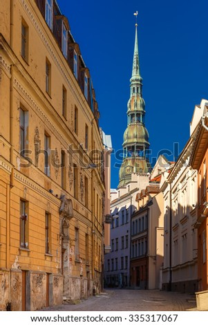 Narrow street of Old Town on a sunny day, Saint Peter church on the background, Riga, Latvia - stock photo