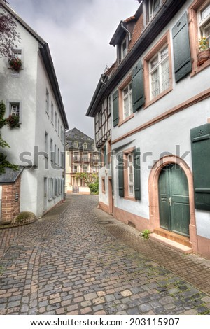 Narrow street with cobblestones between old houses in the historical center of Heidelberg, Germany - stock photo