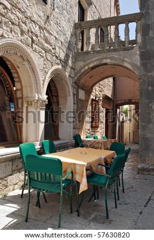 Narrow street with coffee house in old medieval town Korcula by day. Croatia, Dalmatia region, Europe. - stock photo