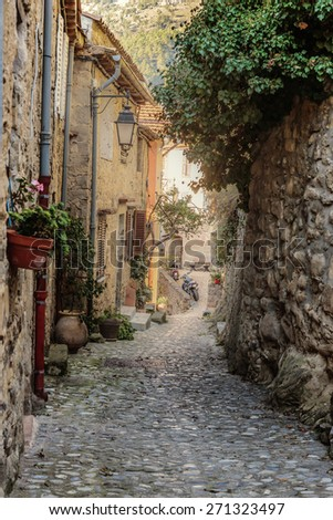 Narrow street with flowers in the old town Coaraze in France - stock photo